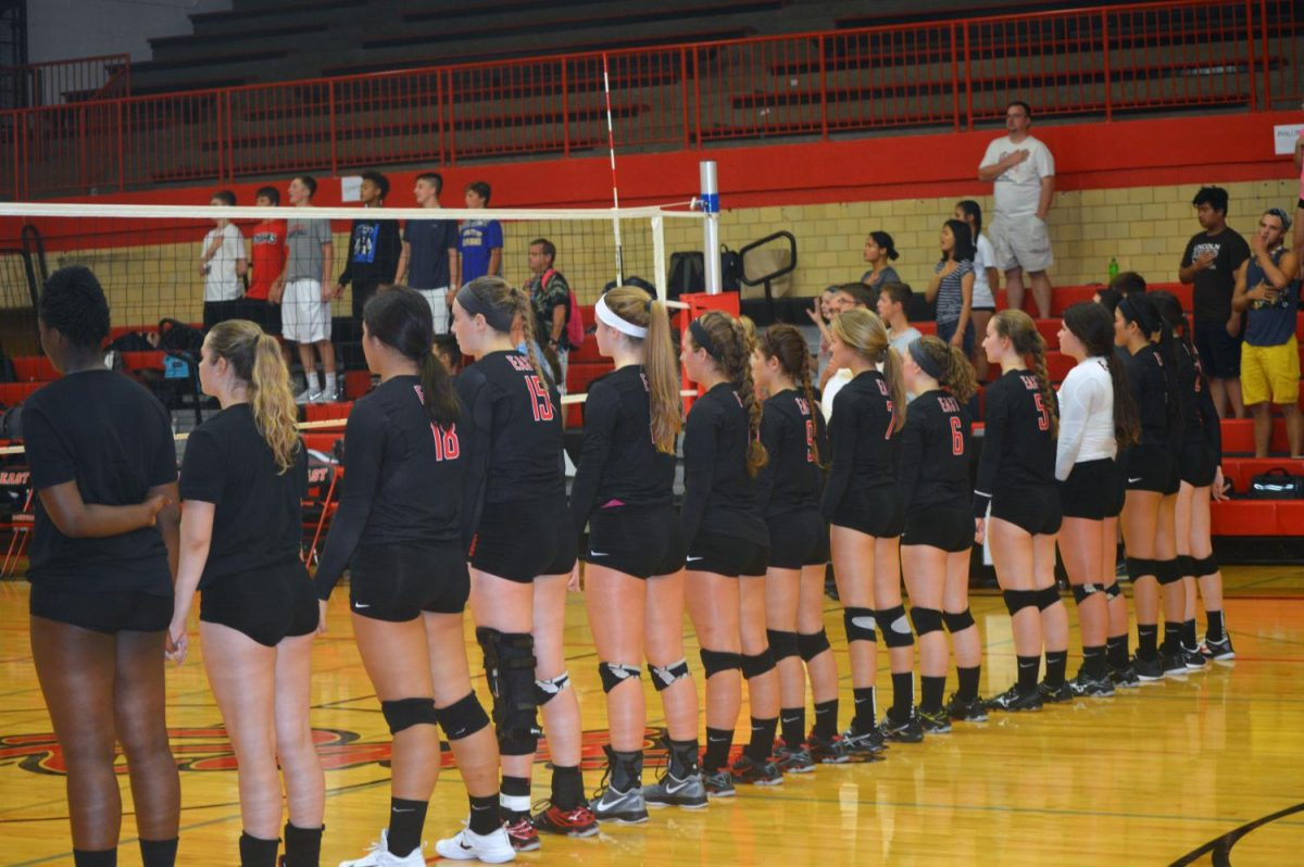 The Lady E-Rabs varsity volleyball team holds hands to unite during the national anthem. The E-Rabs face off against the Guilford Vikings.